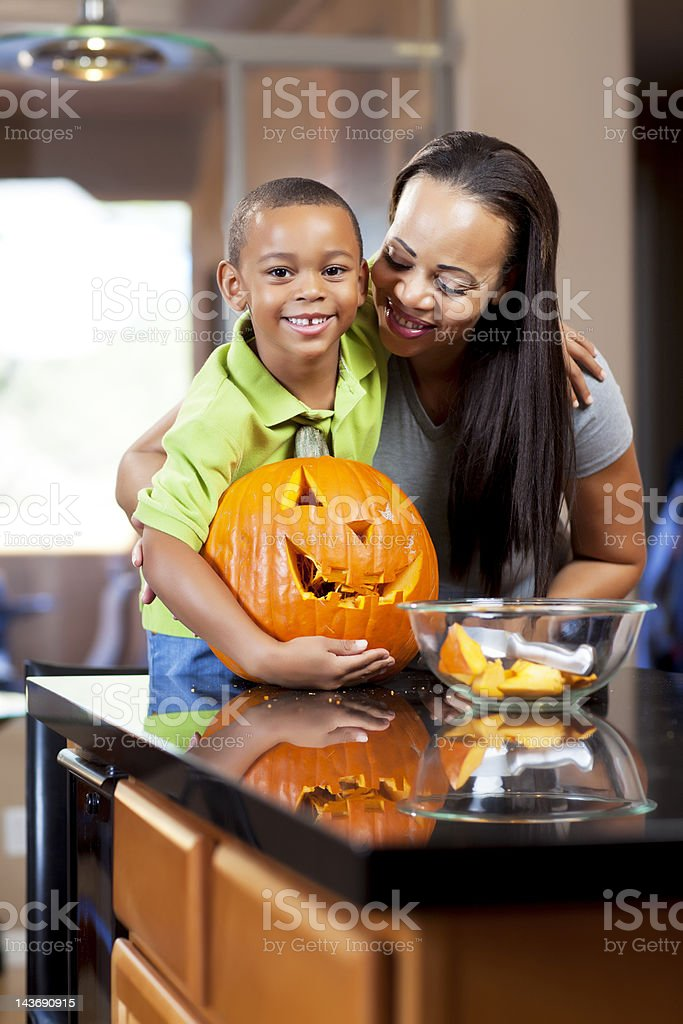 Mother and son carving jack-o-lantern stock photo