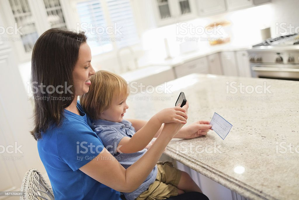 Mother And Son Depositing Check Through Smart Phone stock photo