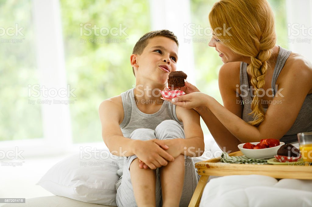 Mother and son eating muffin in bed stock photo