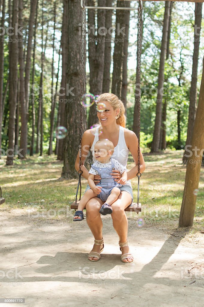 Mother and son enjoying an outdoor playground stock photo