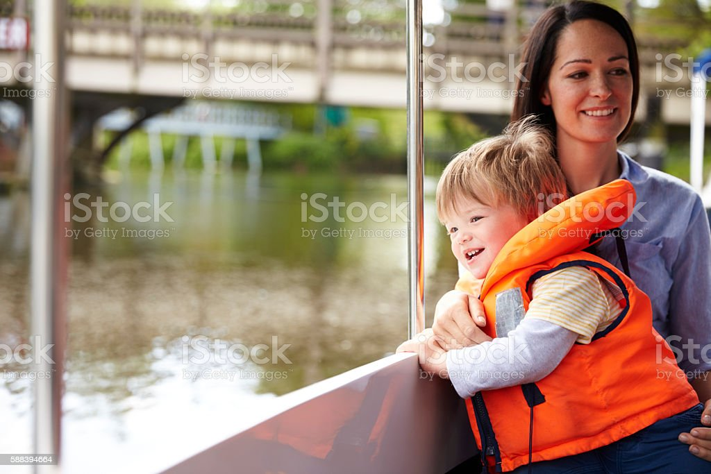 Mother And Son Enjoying Day Out In Boat On River Together stock photo