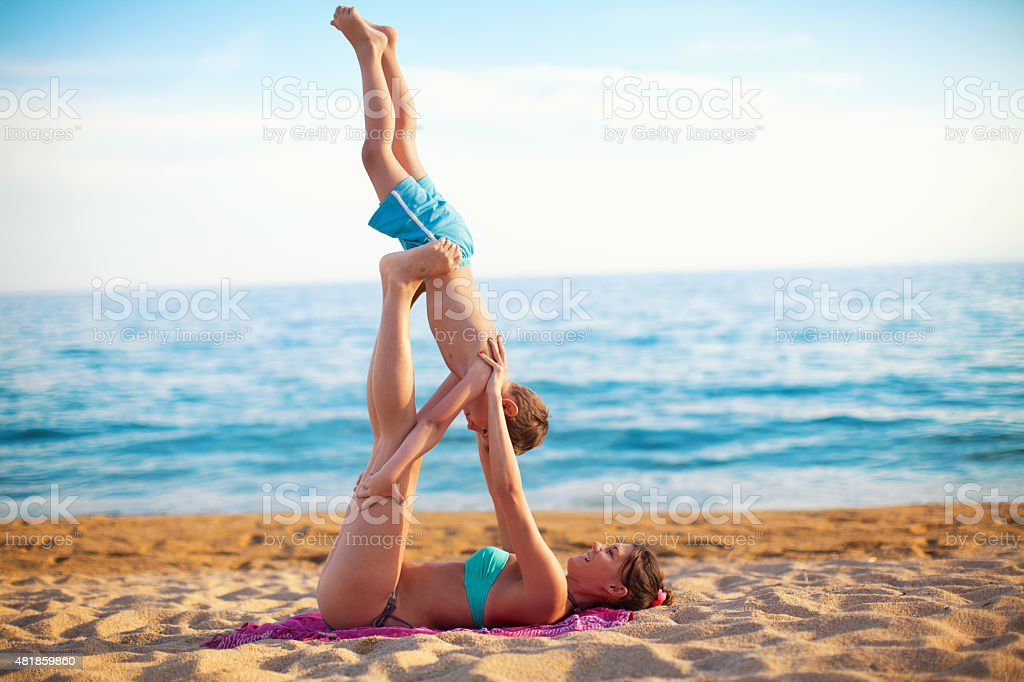 Mother and son exercising on the beach stock photo