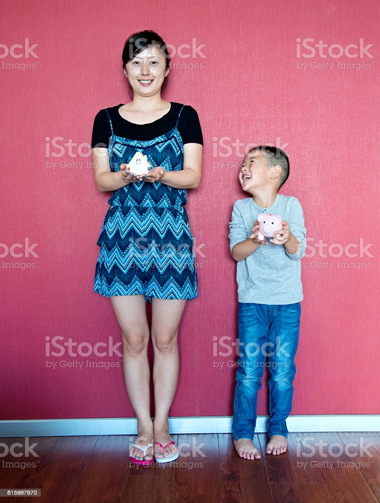 Mother and son hands holding piggy bank and house model stock photo