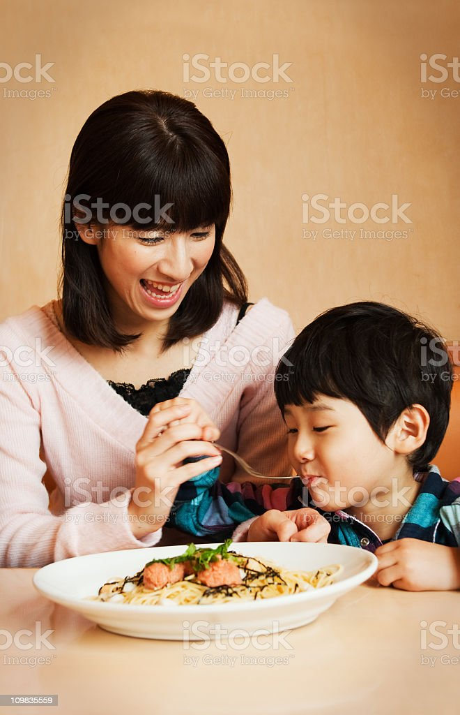Mother and son happily eating spaghetti at the table stock photo