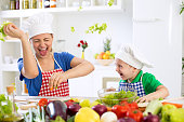 Mother and son have fun in kitchen food war