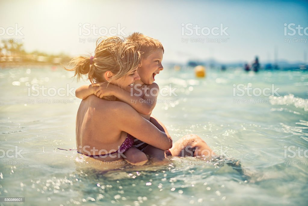 Mother and son having fun in sea stock photo