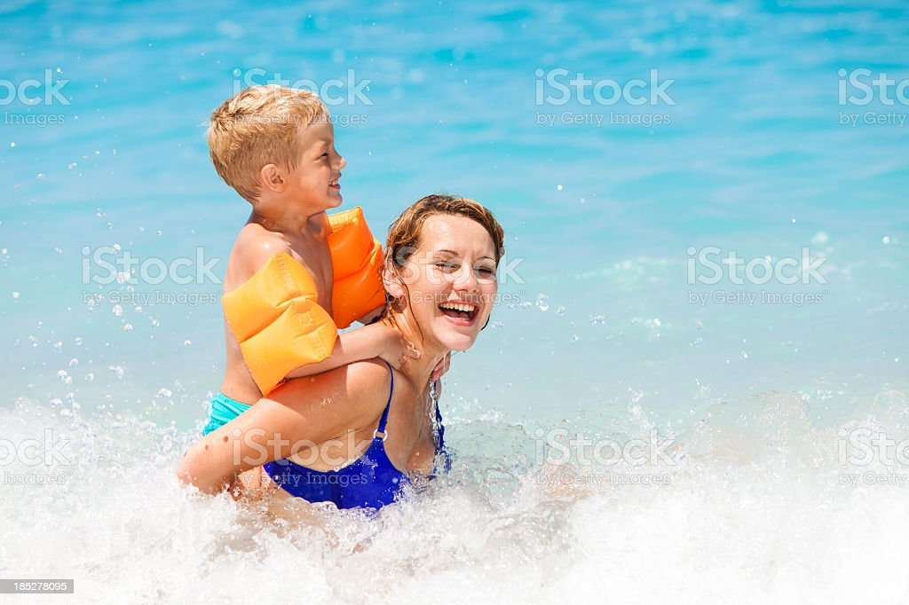 Mother and son having fun on sea waves stock photo