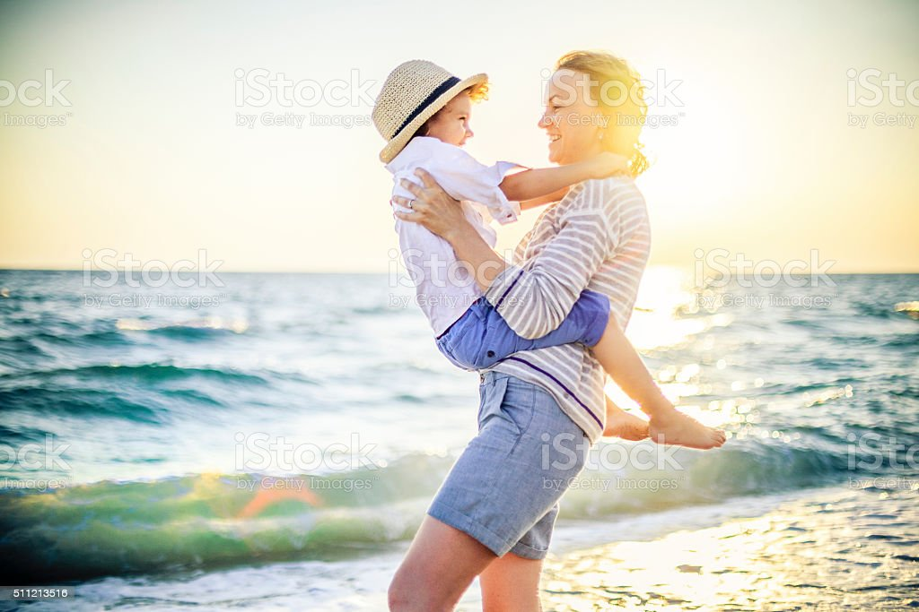 Mother and son having fun on the beach stock photo