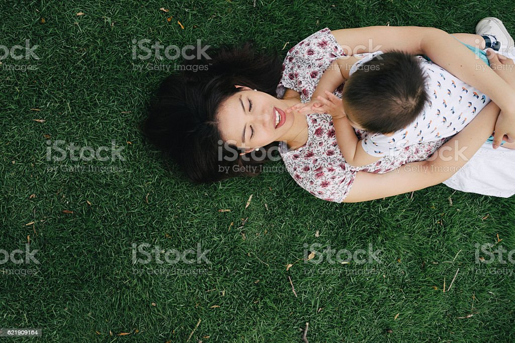 Mother and son having fun together in a park stock photo