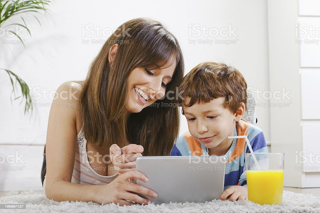 Mother and son having fun with digital tablet at home royalty-free stock photo