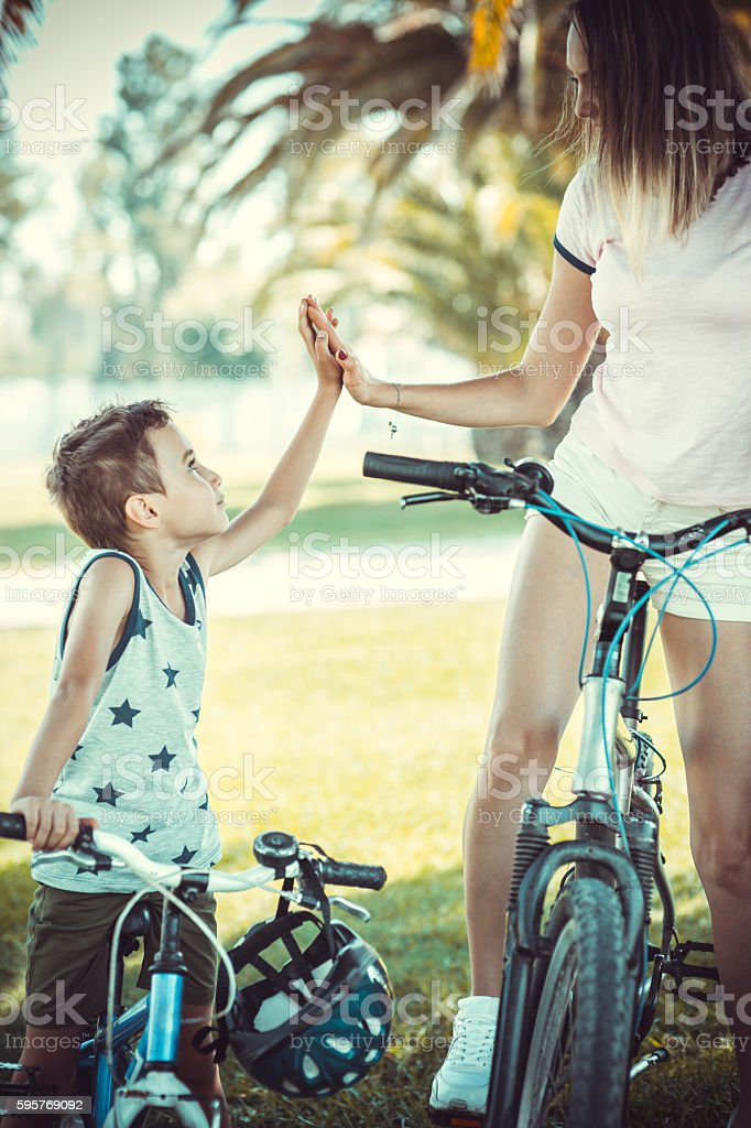 Mother and son 'high five' stay with rented bicycles stock photo
