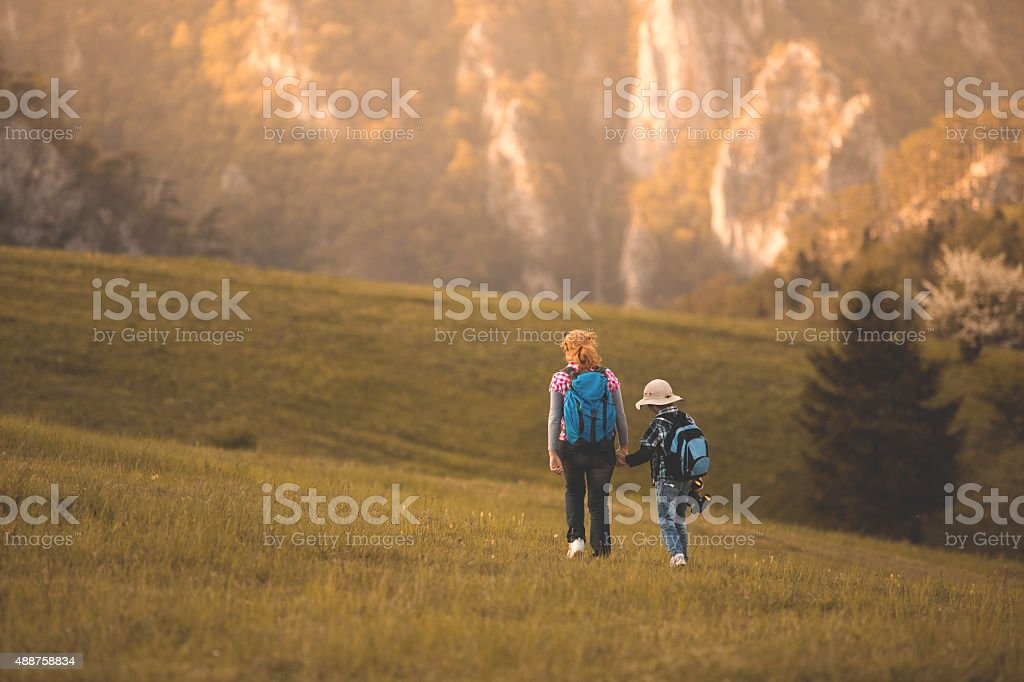 Mother and son hiking along mountain path stock photo