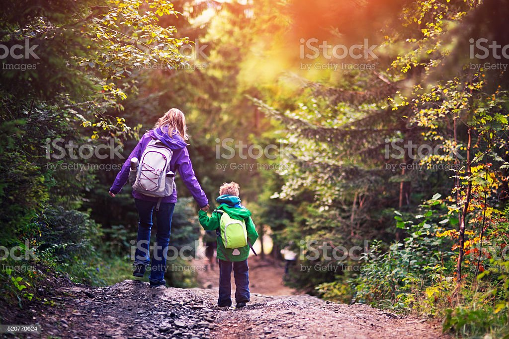 Mother and son hiking in forest. stock photo
