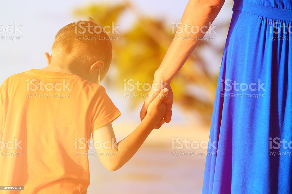 mother and son holding hands on beach stock photo