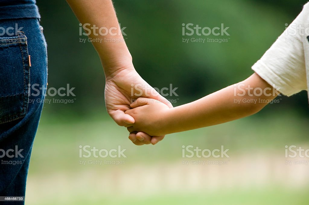 mother and son holding hands stock photo