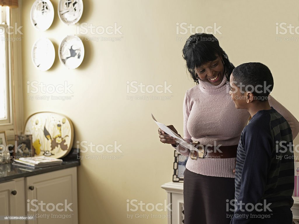 Mother and son (12-13) holding school report card stock photo