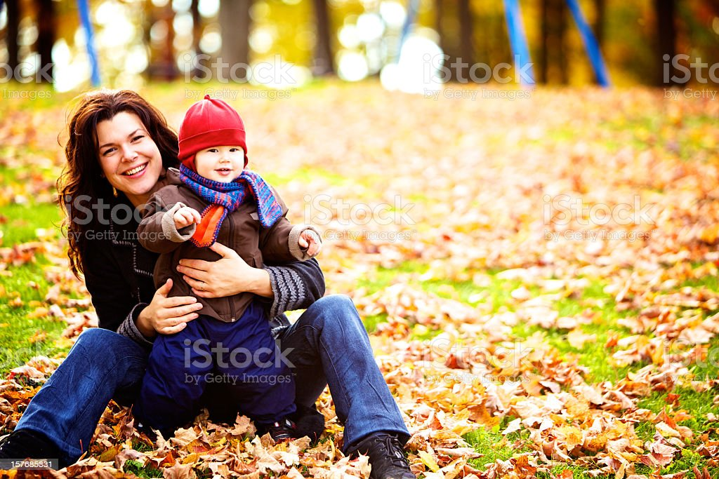 Mother and son in the park with leaves on the ground royalty-free stock photo