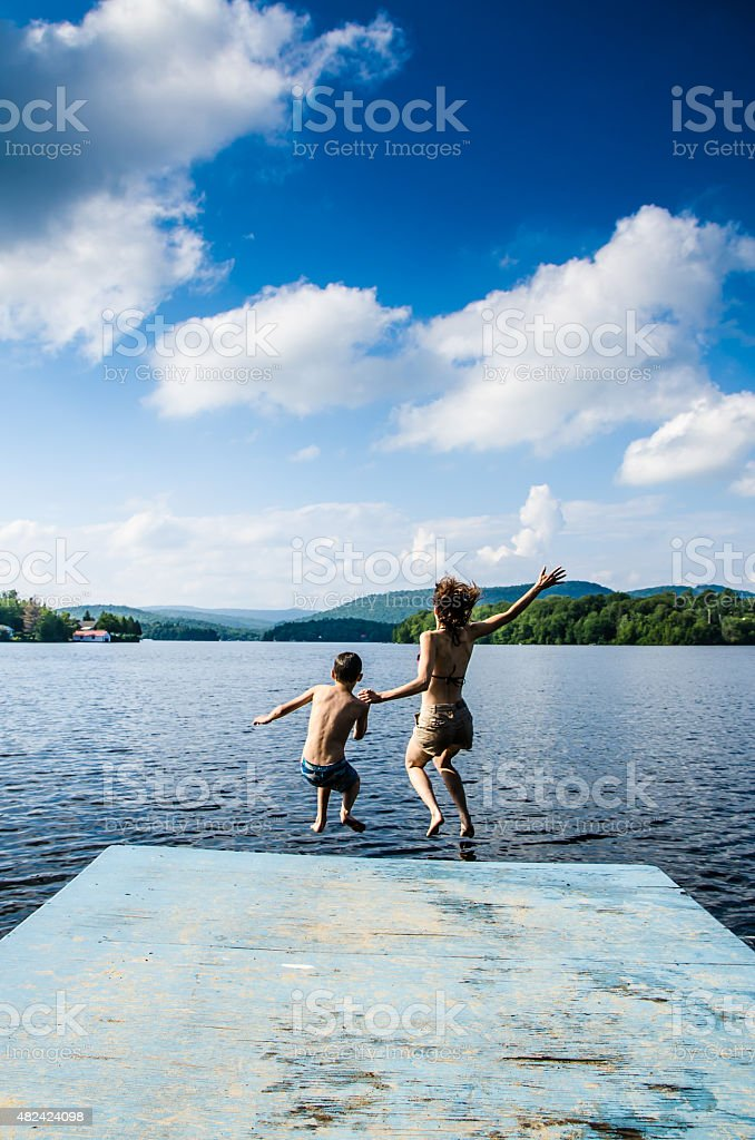 Mother and son jumping in lake from dock stock photo