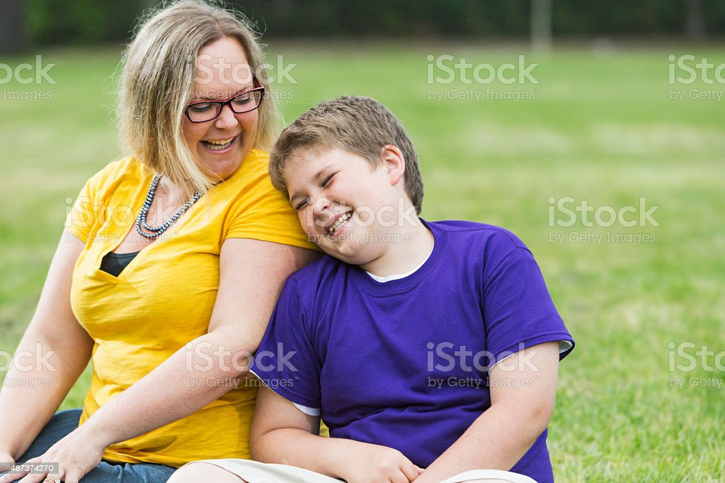 Mother and son laughing in the park stock photo