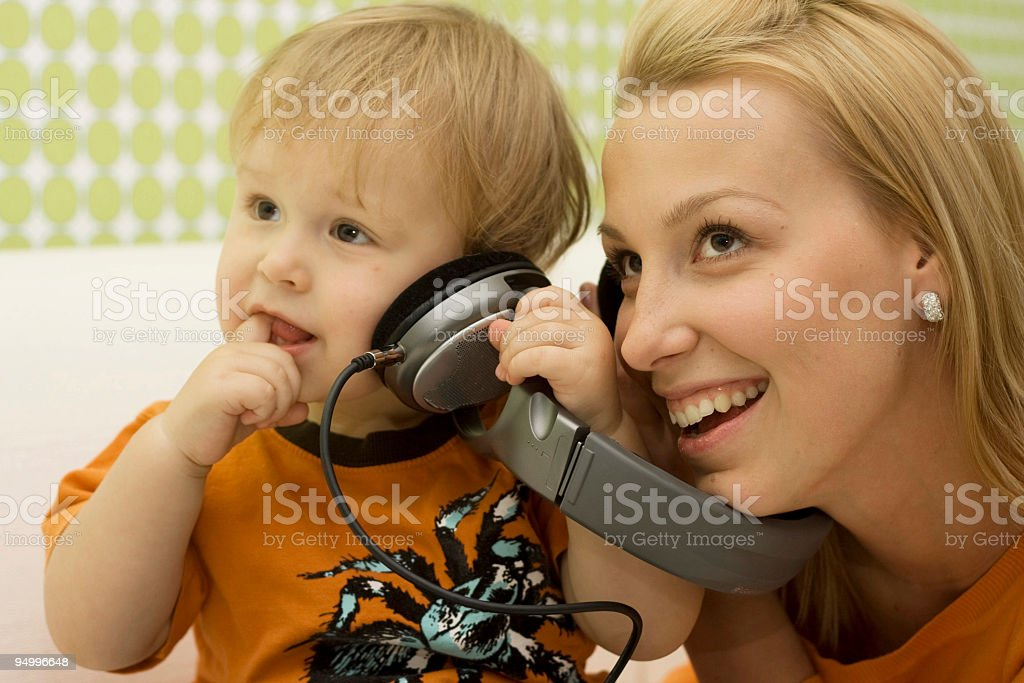 Mother and son listening to music from headphones royalty-free stock photo