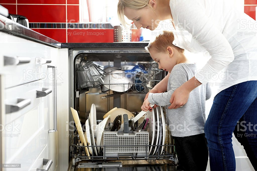 Mother and son loading dishwasher stock photo