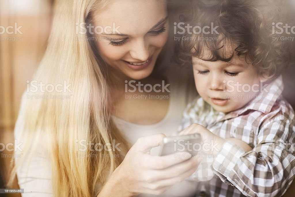 Mother and son looking at mobile phone stock photo