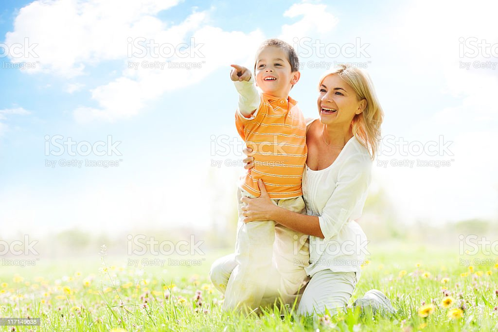 Mother and son looking in distance while relaxing on meadow. royalty-free stock photo