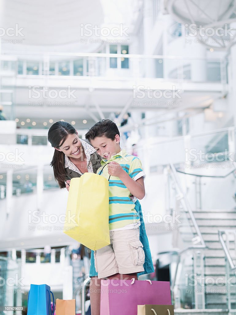 Mother and son looking in shopping bags in mall royalty-free stock photo