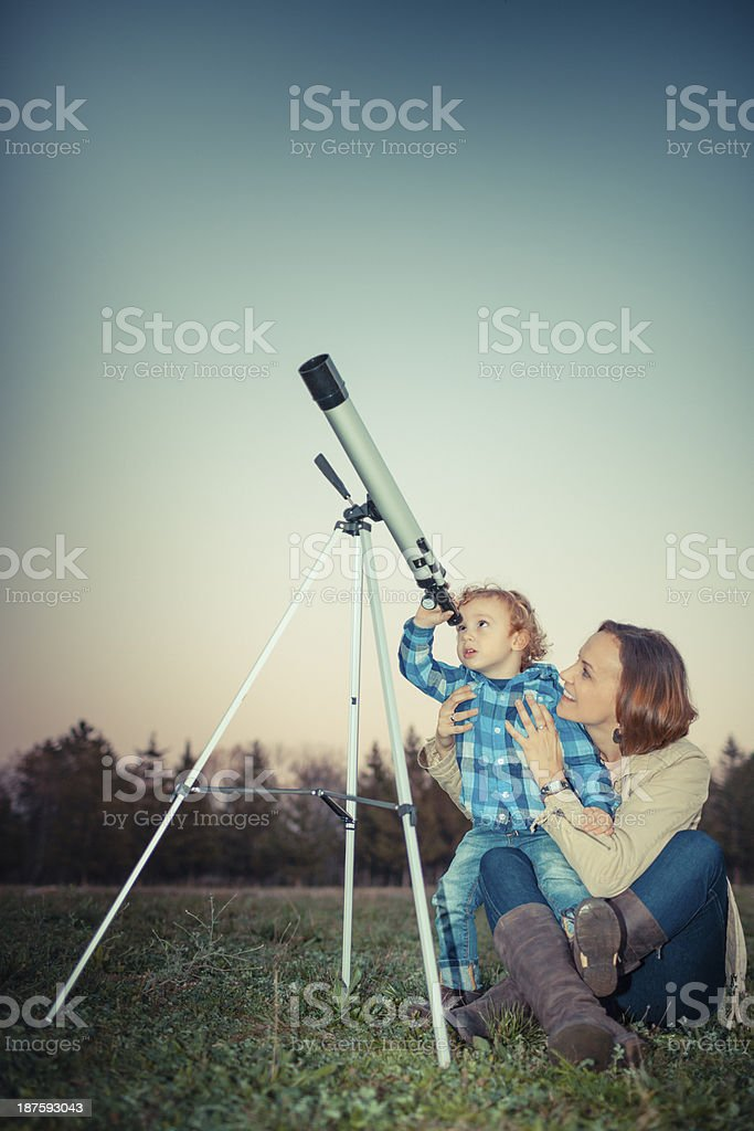 Mother and son looking through a telescope outdoors stock photo