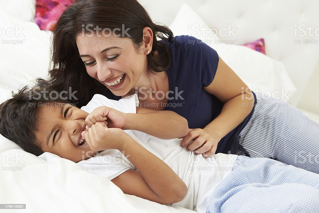 Mother And Son Lying In Bed Together stock photo