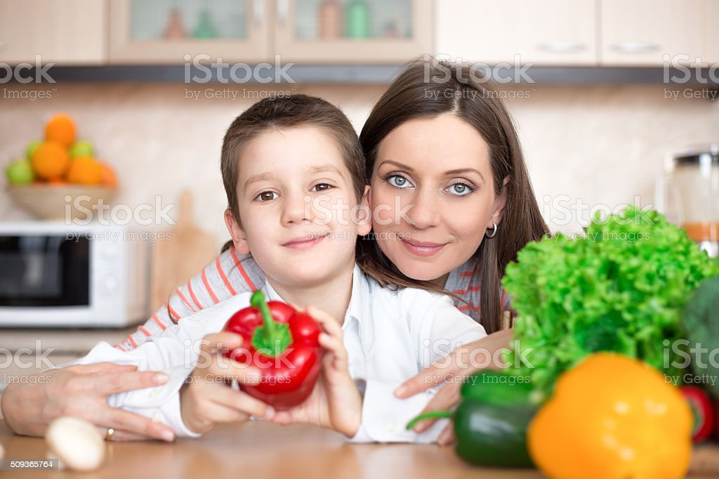 Mother and son making salad in the kitchen stock photo