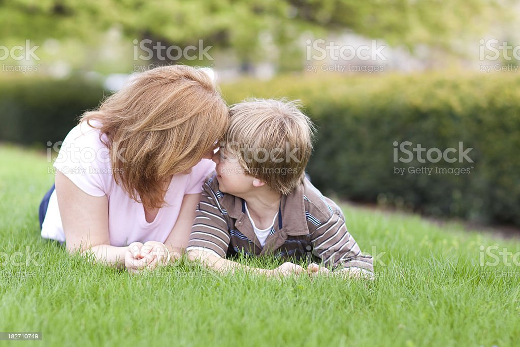 Mother and son on grass cuddling (Series) stock photo