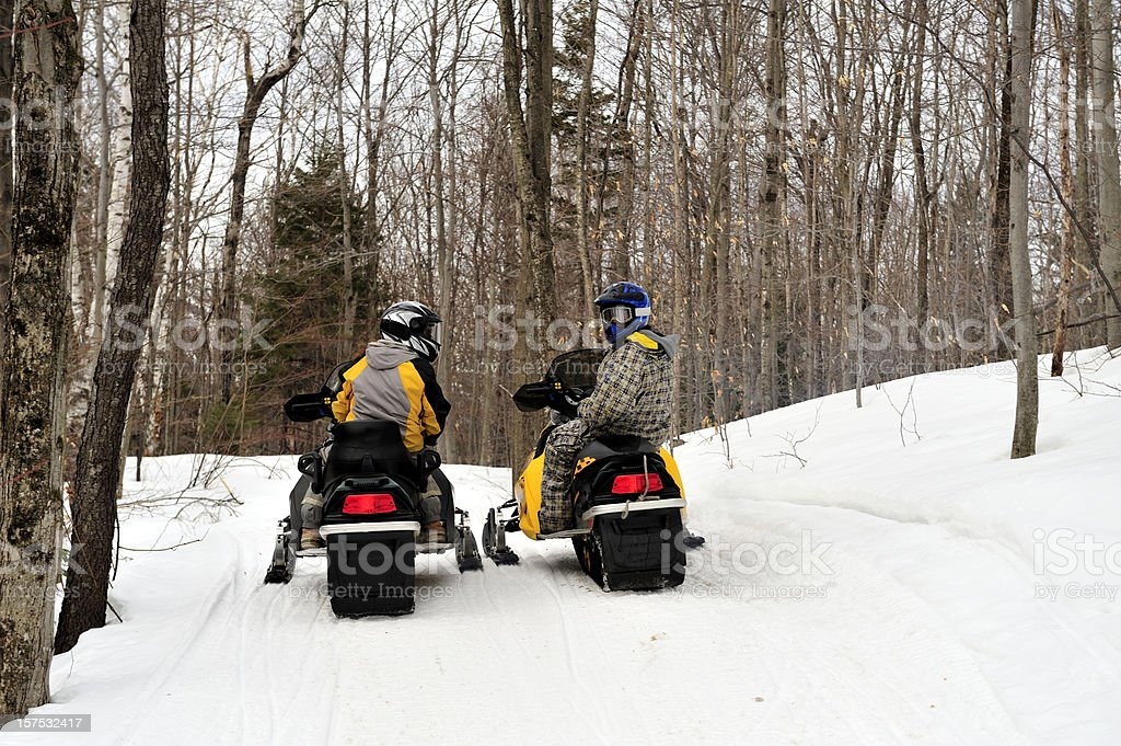 Mother and son on snowmobiles stock photo