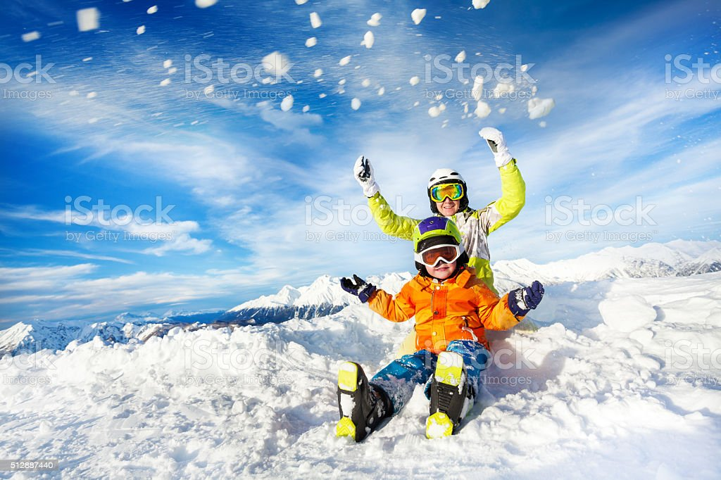 Mother and son on the mountain happy throw snow stock photo