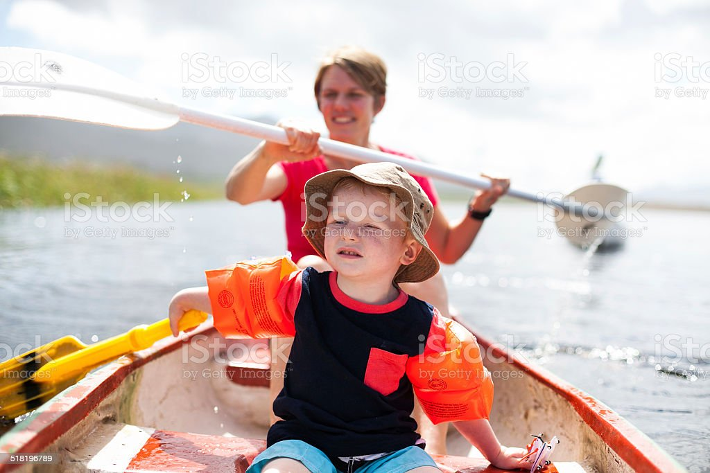 Mother and son paddling on a small boat stock photo