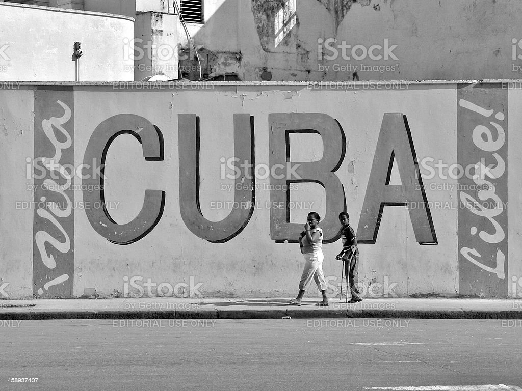 Mother and son passing a wall in Havana Cuba royalty-free stock photo