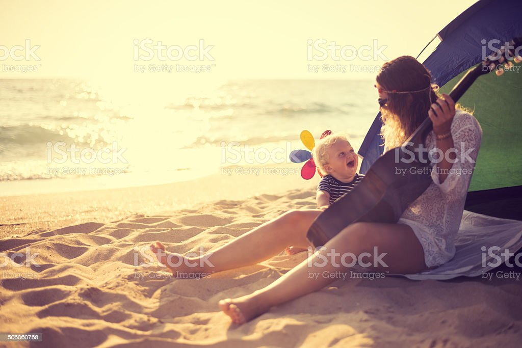 Mother and son playing a guitar on the beach stock photo
