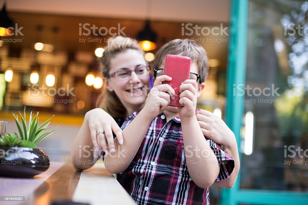 Mother and son playing game on the smartphone. stock photo