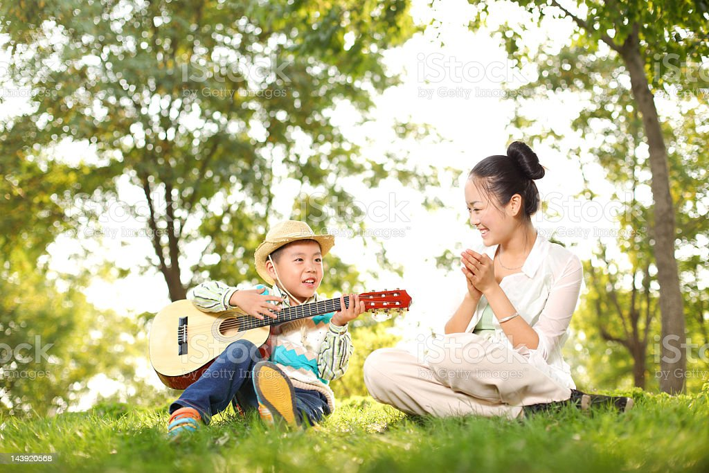 Mother and son playing guitar in the park stock photo
