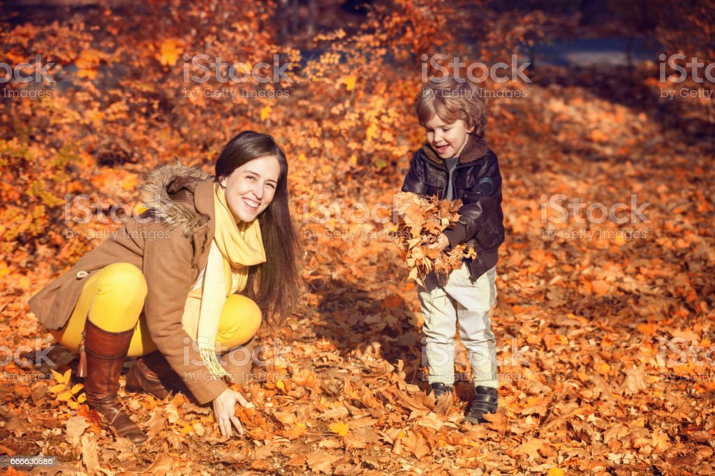 Mother and son playing in autumn. stock photo