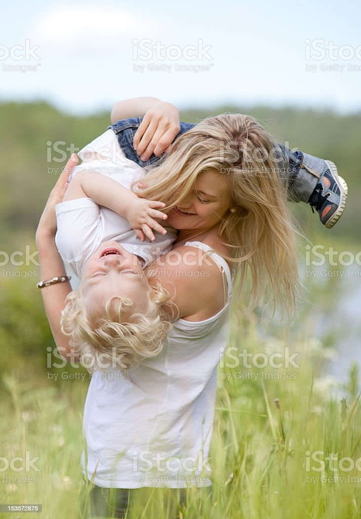 Mother and Son Playing in Meadow stock photo