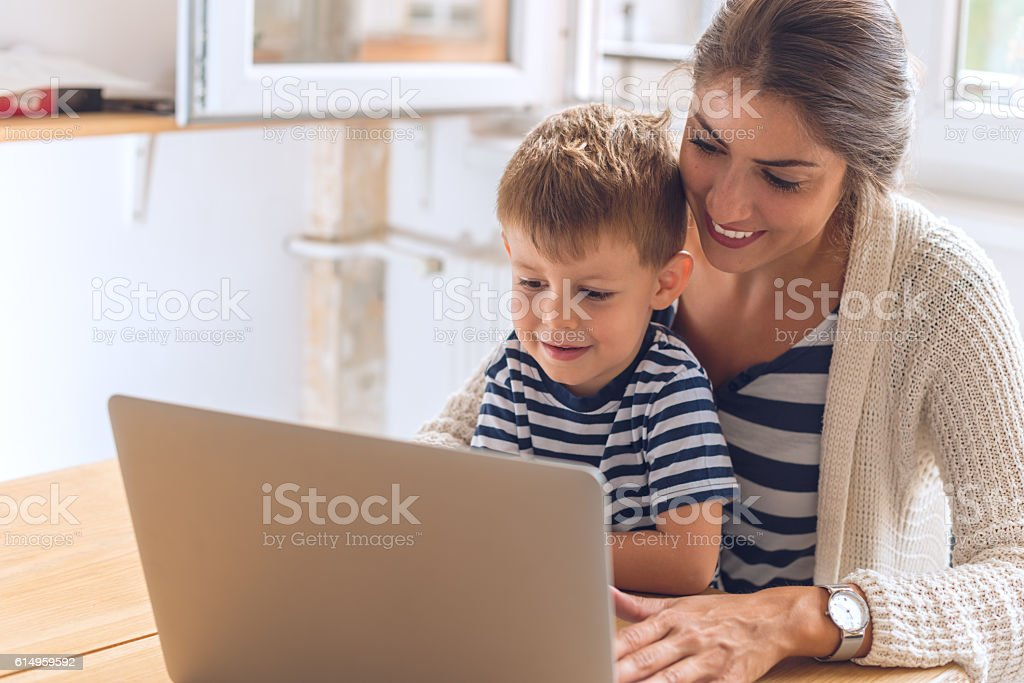 Mother and son playing on a computer stock photo