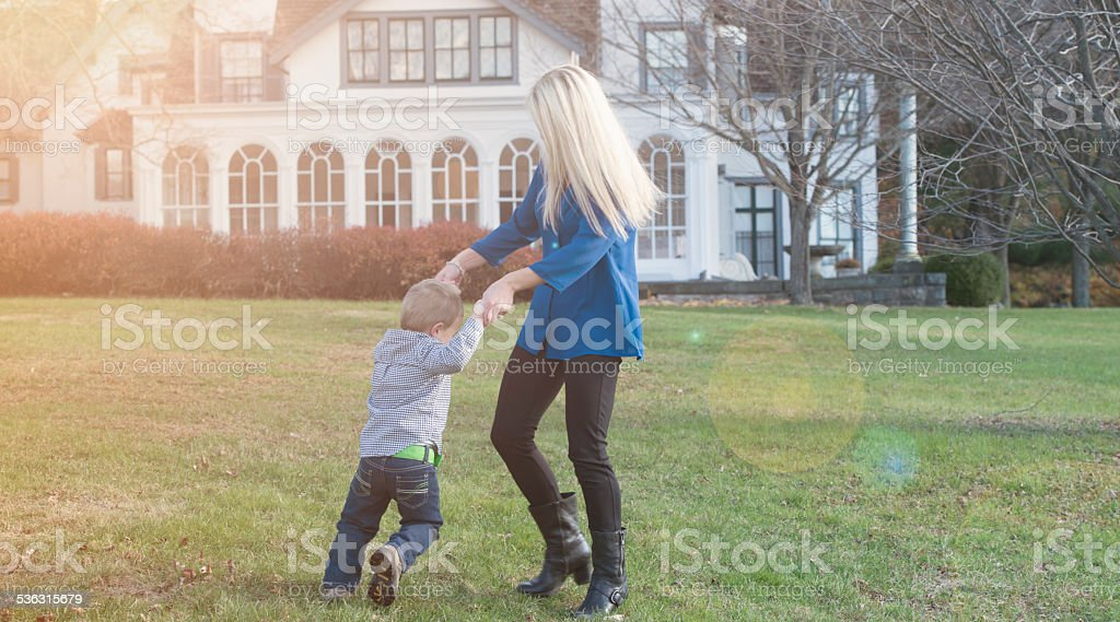 mother and son playing outdoors in the backyard stock photo