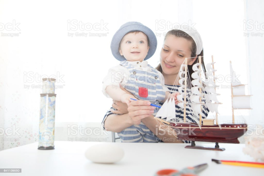 Mother and son playing with the ship. stock photo