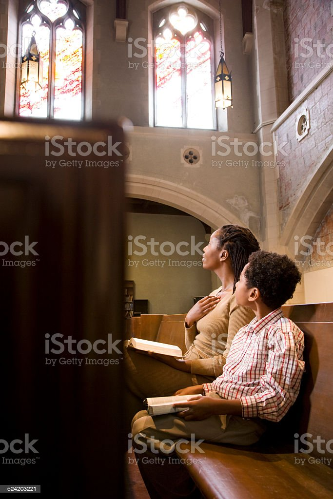 Mother and Son Praying from Bible in Church stock photo