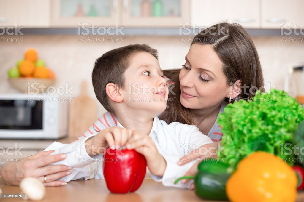 Mother and son preparing food in the kitchen stock photo