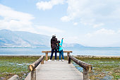 Mother and son raising hands while standing on lakeside jetty