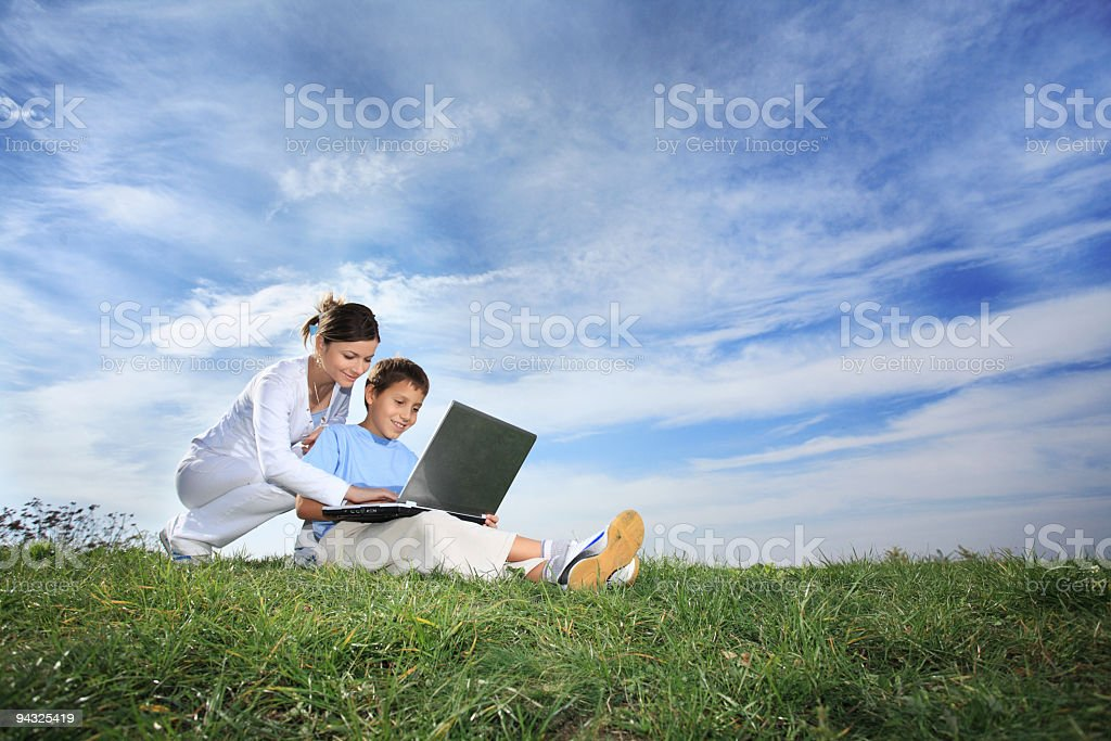 Mother and son resting outdoor with laptop stock photo