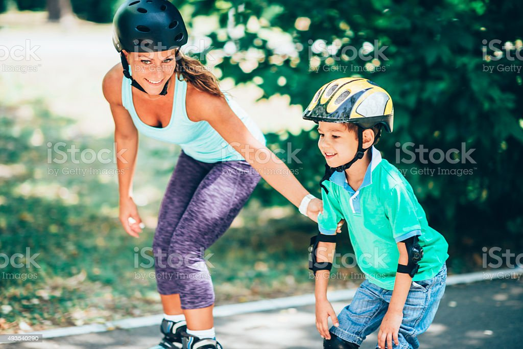 Mother and son roller skating stock photo