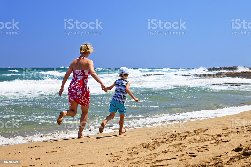 Mother and son running along sandy beach royalty-free stock photo